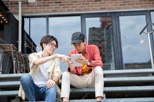 タブレットを見て話す20代男性2人の写真素材 [FYI03400522]
