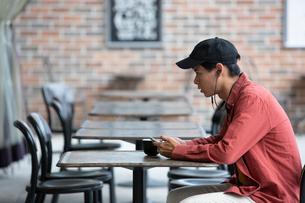 カフェでスマホを見る20代男性の写真素材 [FYI03400547]