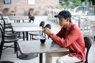 カフェでスマホを見る20代男性の写真素材 [FYI03400602]