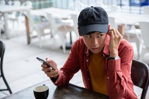 カフェでスマホを見る20代男性の写真素材 [FYI03400603]