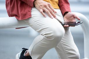 車止めポールに座りスマホを持つ20代男性の写真素材 [FYI03400610]