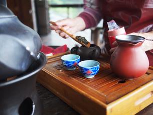 台湾,九份の茶房と茶器と中国茶葉を急須に入れる手元の写真素材 [FYI03401532]