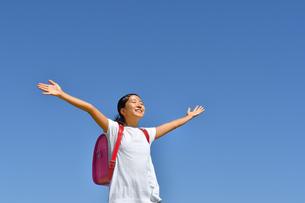 青空でバンザイする小学生の女の子(ランドセル)の写真素材 [FYI03402539]