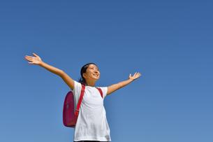 青空でバンザイする小学生の女の子(ランドセル)の写真素材 [FYI03402540]