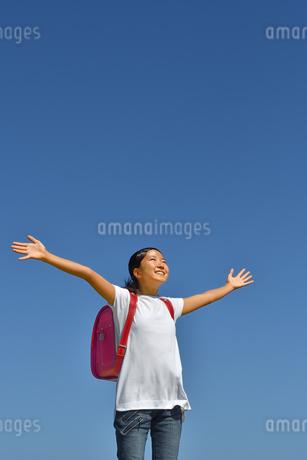 青空でバンザイする小学生の女の子(ランドセル)の写真素材 [FYI03402541]