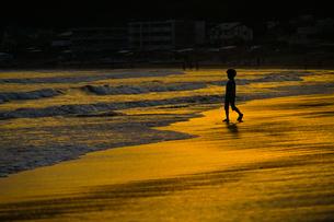 夕暮れの波打ち際で遊ぶ子供の写真素材 [FYI03402641]