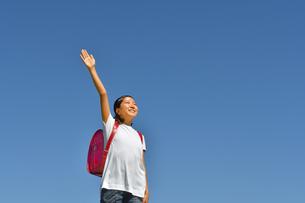 青空で手を挙げる小学生の女の子(ランドセル)の写真素材 [FYI03403398]