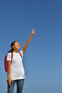 青空でVサインをきめる小学生の女の子(ランドセル)の写真素材 [FYI03403399]
