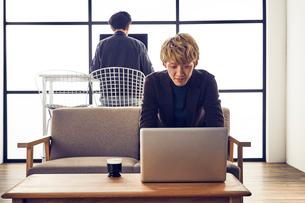 自宅兼オフィスで仕事をする2人の男性の写真素材 [FYI03404044]