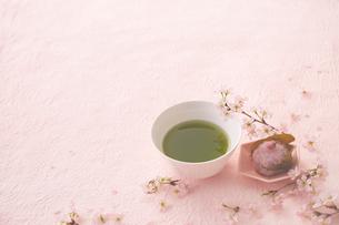 ピンクの和紙の上の抹茶と桜餅とサクラの花の写真素材 [FYI03404074]