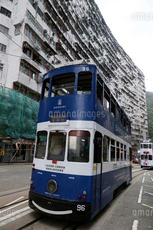 香港島のモンスターマンションの前を行く路面電車トラムの写真素材 [FYI03406212]