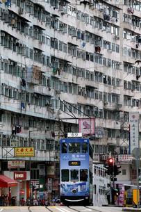 香港島のモンスターマンションの前を行く路面電車トラムの写真素材 [FYI03406214]