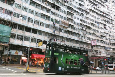 香港島のモンスターマンションの前を行く路面電車トラムの写真素材 [FYI03406215]
