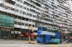 香港島のモンスターマンションの前を行く路面電車トラムの写真素材 [FYI03406216]