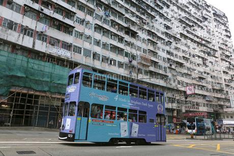香港島モンスターマンションの前を行く路面電車トラムの写真素材 [FYI03406217]