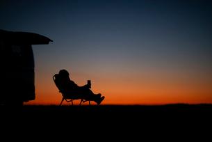 椅子に座る男性と車のシルエットの写真素材 [FYI03406378]
