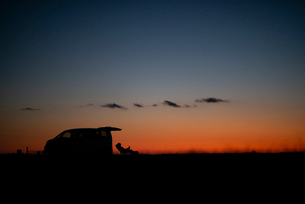 椅子に座る男性と車のシルエットの写真素材 [FYI03406379]