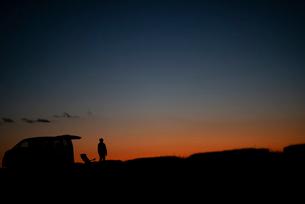 遠くを眺める男性と車のシルエットの写真素材 [FYI03406382]