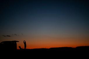 伸びをする男性と車のシルエットの写真素材 [FYI03406384]