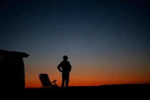 遠くを眺める男性と車のシルエットの写真素材 [FYI03406387]