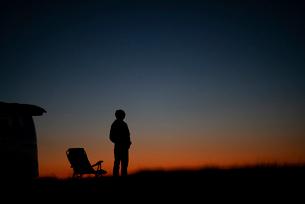 遠くを眺める男性と車のシルエットの写真素材 [FYI03406389]