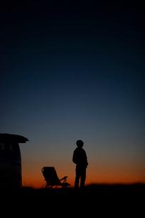 遠くを眺める男性と車のシルエットの写真素材 [FYI03406391]