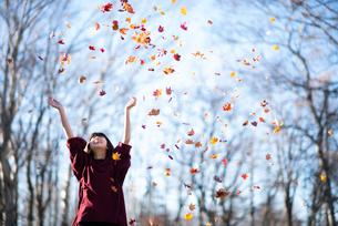 落ち葉を巻き上げる女性の写真素材 [FYI03406661]