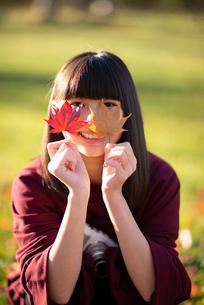 紅葉から顔を覗かせる女性の写真素材 [FYI03406672]