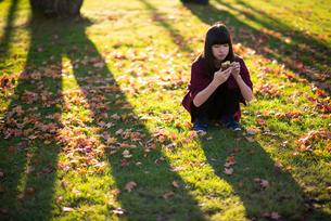 焼き芋を食べる女性の写真素材 [FYI03406681]