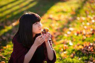 焼き芋を食べる女性の写真素材 [FYI03406683]