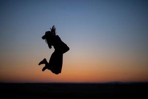 夕焼けの中でジャンプする女性のシルエットの写真素材 [FYI03406702]