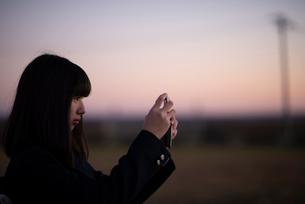 夕焼けの中で写真を撮る女性の写真素材 [FYI03406708]