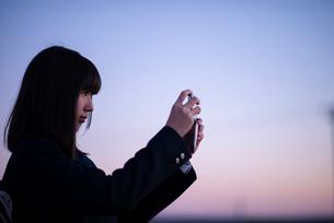 夕焼けの中で写真を撮る女性の写真素材 [FYI03406709]
