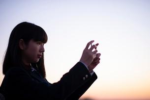 夕焼けの中で写真を撮る女性の写真素材 [FYI03406710]