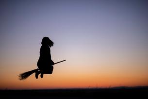 夕焼けの中でほうきに乗る女性のシルエットの写真素材 [FYI03406714]