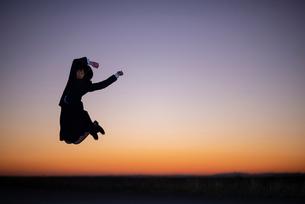 夕焼けの中でジャンプする女性の写真素材 [FYI03406715]