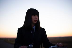 夕焼けの中で自転車を押す女性の写真素材 [FYI03406728]