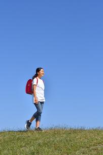 青空で歩く小学生の女の子(ランドセル)の写真素材 [FYI03406780]
