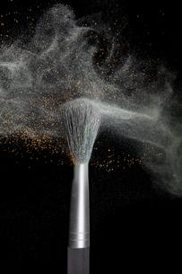 化粧筆と飛散るカラーパウダーの写真素材 [FYI03406867]