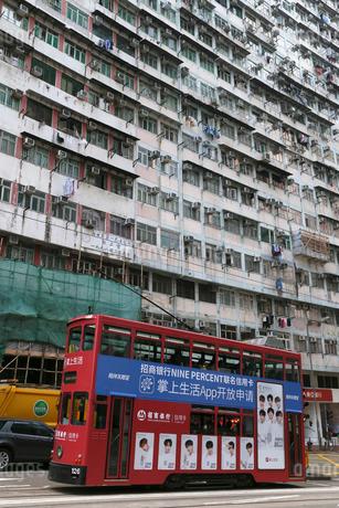 香港島のモンスターマンション前を行く路面電車トラム。英国植民地時代からあるの写真素材 [FYI03407709]