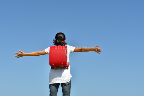 青空で両手を広げる小学生の女の子(後姿)の写真素材 [FYI03408457]