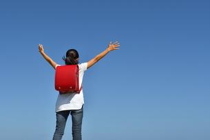 青空でバンザイする小学生の女の子(後姿)の写真素材 [FYI03408459]