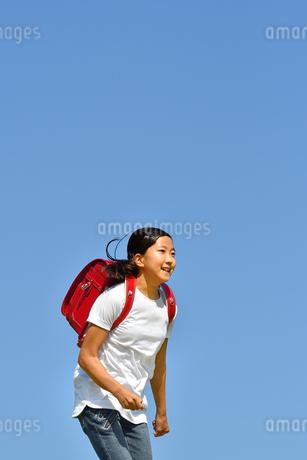 青空で走る小学生の女の子(ランドセル)の写真素材 [FYI03409099]