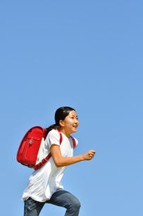 青空で走る小学生の女の子(ランドセル)の写真素材 [FYI03409100]