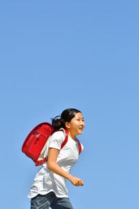 青空で走る小学生の女の子(ランドセル)の写真素材 [FYI03409101]