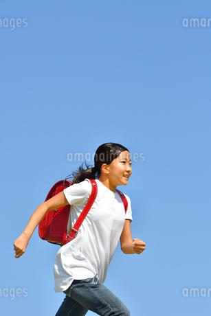 青空で走る小学生の女の子(ランドセル)の写真素材 [FYI03409102]