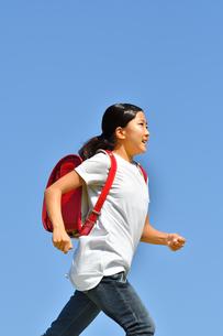 青空で走る小学生の女の子(ランドセル)の写真素材 [FYI03409106]