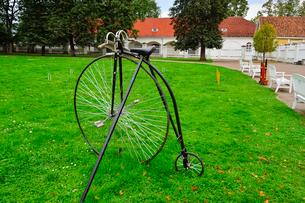 エストニア・北部にある18世紀の建物でエストニアで最も早く修復された領主の館のパルムセの館(現在は公園の情報センターや博物館として使用)の庭園に置かれている自転車の写真素材 [FYI03409387]