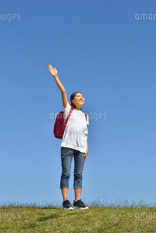 青空で手を上げる小学生の女の子(ランドセル)の写真素材 [FYI03409795]