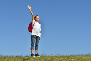 青空で手を上げる小学生の女の子(ランドセル)の写真素材 [FYI03409796]